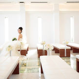 【新館Hiyoriチャペル】 シンプルだけど高級感のある内装で、花嫁のウェディングドレス姿をより一層ひきたてます。 背もたれのないベンチはお着物の方でも安心。最大90名様まで着席可能です。