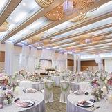 天井高があり広々とした空間 高さを活かしたプロジェクションマッピングや大迫力での映像演出が可能。 木目調の高級感を感じる壁面に、やわらかなドレープと光で華やかさと 特別感を創り上げたドラマティックな披露宴会場