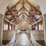 ステンドグラスが輝く神聖な空間。木目を使用したチャペルは木の温もりを感じさせてくれる。