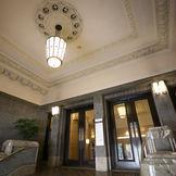 天井に松笠などの植物をモチーフにした立体感のあるモールディング(縁飾り)が付く正面玄関