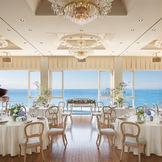 高さ約4Mを誇る窓からの眺望は、まさに『圧巻』の一言。フローリストが創り出す独特のコーディネートに、一目惚れするカップルが続々。メインバックに広がる美しい空と海が祝宴に華を添える