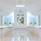 白を基調としたチャペル!正面のステンドグラスはロンドン郊外の教会で使用されていたものです。差し込む光がお二人を祝福します。