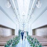 チャペルには、直径85mmのスワロフスキークリスタルを組み合わせて作られた十字架と、 ガラスアーティストのパイオニア 野口真里氏による高さ9メートルのガラスウォールから差し込む虹色の煌めきが、 大理石のバージンロードにふりそそぐ幻想的な空間に。