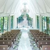 陽光のシャワー、祭壇奥に流れる滝のベール、きらめく緑がふたりを祝福する森の中の独立型チャペル