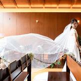 ウッド調のチャペルは白ドレスを美しく際立てます。 バージンロードはゆとりのある広さで、一歩一歩ゆっくりと入場して頂けます。