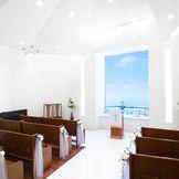 大きな窓から海を臨む白亜のチャペルは着席最大40名まで、立見を含めると50名まで収容。