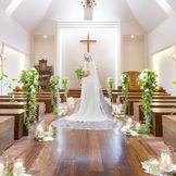 木目調のバージンロードに白いウェディングドレスが映える
