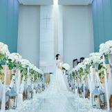 天井高10mの透明感あふれるチャペルにはあたたかな自然光が降り注ぎます。 大理石のバージンロードも10mと都内有数の開放感。 プロジェクションマッピングの演出が挙式をさらに感動で彩ります。