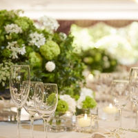 白とグリーンで窓から見える緑との統一感を感じさせるテーブル装花