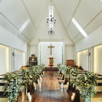 ウォールナット天然木のバージンロードを備え、緑と光に包まれた「木の教会」
