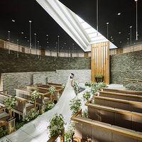 木製の扉を開いて正面に見えるのはモダンなデザインの祭壇。真っ白な大理石のバージンロードと天井が鮮やかなコントラストを織りなす。グリーンと石に包まれる円形の空間で都会のオアシスを感じる感動的なチャペル