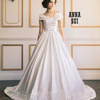 美しいドレープが大胆にクロスするオフショルダーデザイン。女性らしい柔らかさを醸し出す上質なサテンを使用し、スカートの裾を抜いた部分にはフラワーケミカルレースを一周に施したアナ スイのドレス。